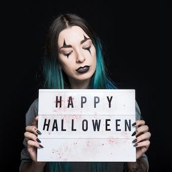 Dziewczyna z strasznym makeup mienia signboard