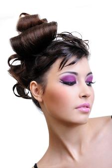 Dziewczyna z stylową fryzurą mody i jasnym fioletowym makijażem