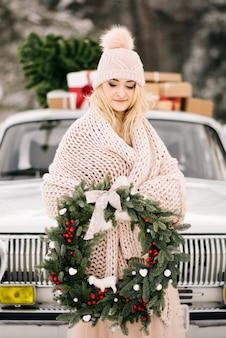 Dziewczyna z świątecznym wieńcem w dłoniach pokrytym kocem i stoi na tle retro samochodu, którego dach to choinka i prezenty w zimowym śnieżnym lesie.
