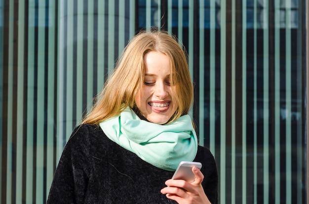 Dziewczyna z szelkami radośnie patrzy na telefon i uśmiecha się. imbirowa kobieta z uśmiechem czyta wiadomość, otrzymuje dobre wieści.