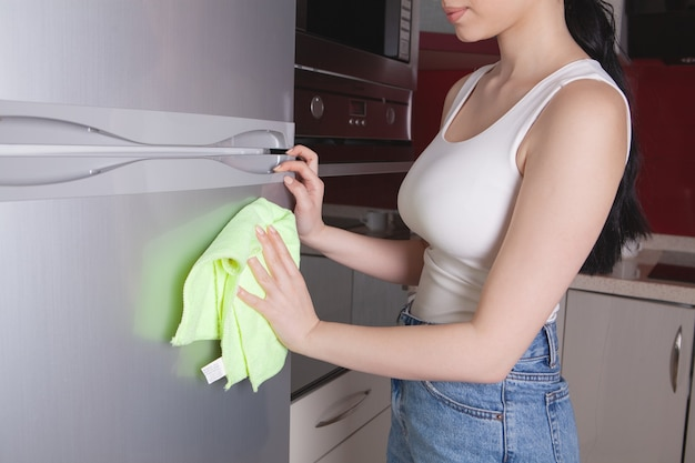 Dziewczyna z szmatką do czyszczenia lodówki
