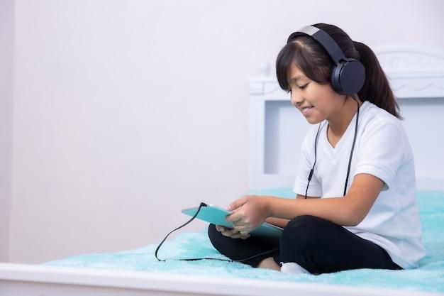 Dziewczyna z tabletem i słuchawki w kwarantannie