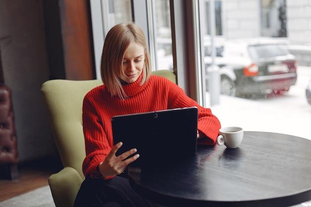 Dziewczyna z tabletem. kobieta w kawiarni. pani siedząca przy stole.