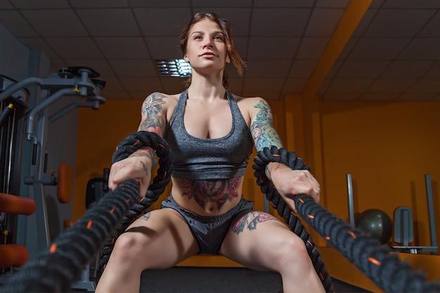 Dziewczyna z tatuażami na fitness robi ćwiczenia z linami