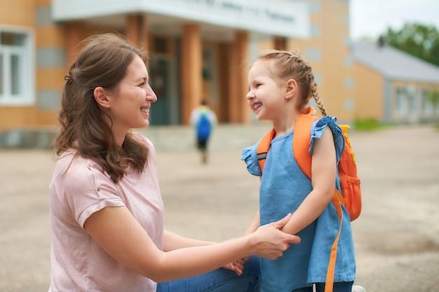 Dziewczyna z teczkami w pobliżu szkoły.
