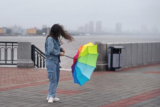 Dziewczyna z tęczowym parasolem na nasypie w deszczowy, wietrzny dzień