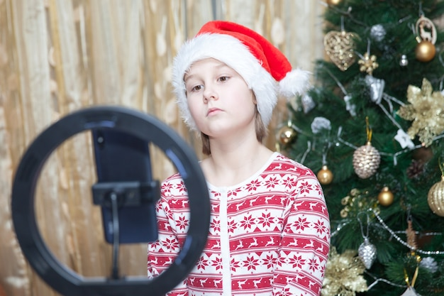 Dziewczyna z telefonem i pierścieniem led lampka w pobliżu choinki