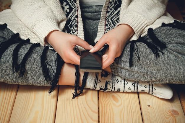 Dziewczyna z telefonem w dłoniach, siedząc na drewnianej podłodze.