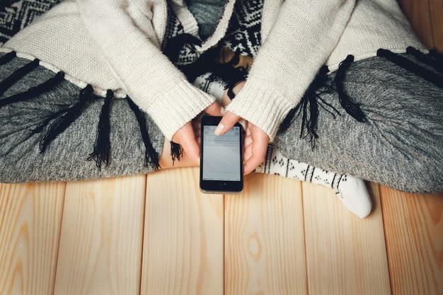 Dziewczyna z telefonem w dłoniach, siedząc na drewnianej podłodze