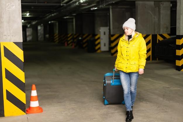 Dziewczyna z torbą na parkingu na lotnisku