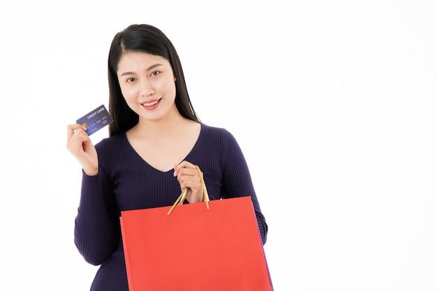 Dziewczyna z torby na zakupy i kart kredytowych w białym tle zadowolony z zakupami