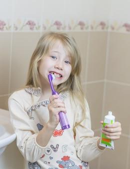 Dziewczyna z tubką pasty do zębów i szczoteczki do zębów w łazience.