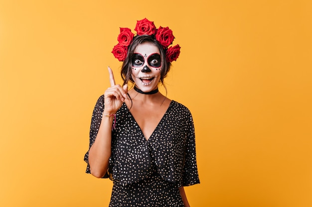 Dziewczyna z twarzą namalowaną na halloween ma nowy zabawny pomysł. portret stylowej młodej kobiety z różami we włosach.