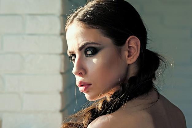 Dziewczyna z twarzy warkocz i makijaż na białym murem