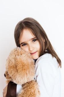 Dziewczyna z ulubionym misiem, dzieciństwo i opieka, rodzina i przyjaciele. dziewczyna bawić się zabawkę i ściska