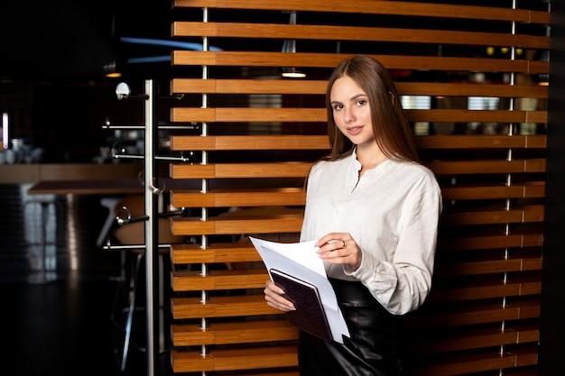 Dziewczyna z uroczym uśmiechem w czarnej spódnicy i białej koszuli z dokumentami w dłoniach