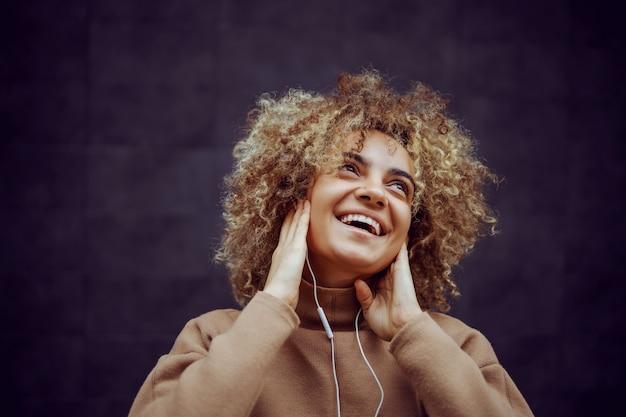 Dziewczyna z uśmiechem na twarzy, trzymając ręce na uszach i słuchając muzyki.