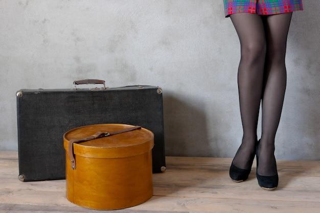 Dziewczyna z walizką i pudełkiem na kapelusze w pustym pokoju