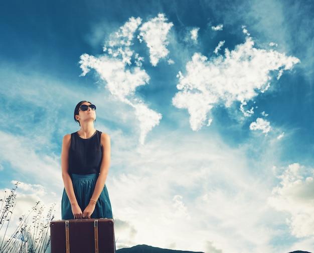 Dziewczyna z walizką w ręku wyobraża sobie podróżowanie po świecie