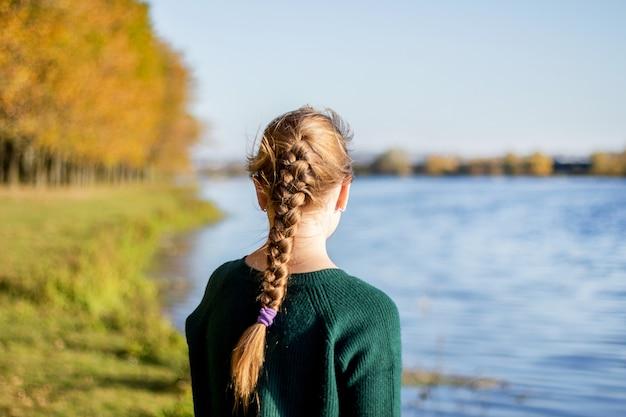 Dziewczyna z warkoczykiem stoi jesienią nad brzegiem rzeki