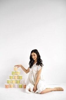 Dziewczyna z wieżą kolorowych pudełek papierowych. zdjęcie do promocji jedzenia na wynos. portret studyjny.