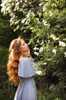 Dziewczyna z włosami i makijażem w liliowej sukience pod kwitnącym drzewem latem w ogrodzie