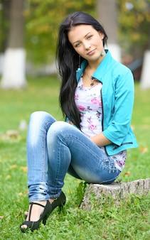Dziewczyna z włosami siedzi na pniu w parku