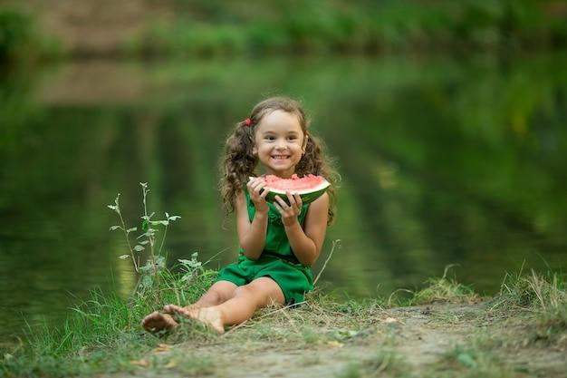 Dziewczyna z włosów galonowe jedzenie arbuza w pobliżu jeziora