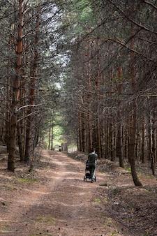 Dziewczyna z wózkiem spaceruje po lesie