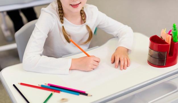 Dziewczyna z wysokim kątem pisania na pusty notatnik