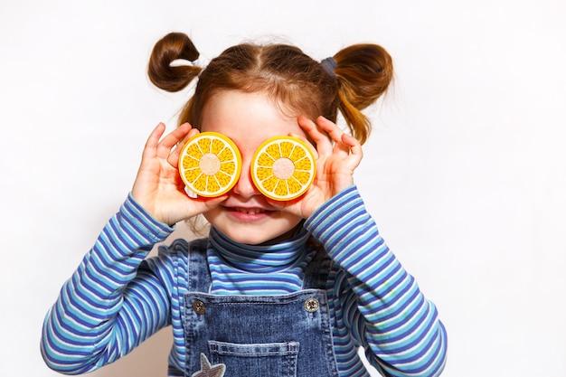 Dziewczyna z zabawkami pomarańczowymi połówkami dla oczu na białym tle. dziecko bawi się pokrojonymi plastikowymi owocami na rzep. gotowanie dla dzieci, dziewczyna uczy się gotować. zbliżenie, portret.