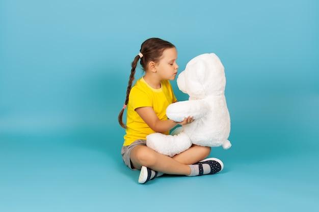 Dziewczyna z zamkniętymi oczami siedzi ze skrzyżowanymi nogami na podłodze, przytula i całuje białego misia