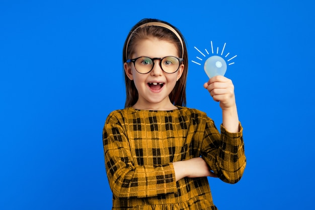 Dziewczyna z żarówką uśmiecha się, mając genialny pomysł na niebieskiej ścianie