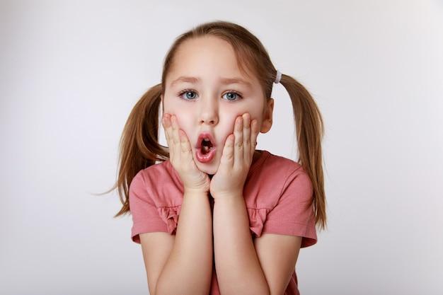 Dziewczyna z zaskoczeniem, cierpiąca na ból zęba, trzymając jej policzek