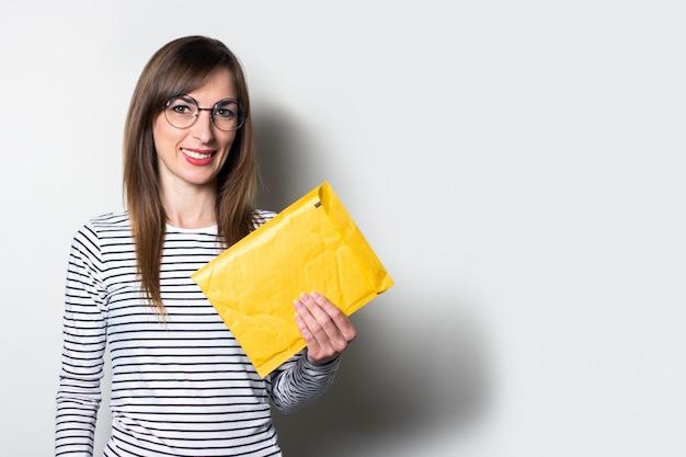 Dziewczyna z zdziwioną twarzą trzyma kopertę z dokumentami na jasnym tle