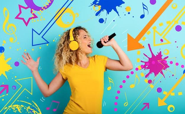 Dziewczyna z zestawem słuchawkowym słucha muzyki i piosenki z mikrofonem. ekspresja emocjonalna i energetyczna.