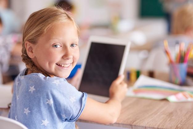 Dziewczyna za pomocą cyfrowego tabletu w szkole