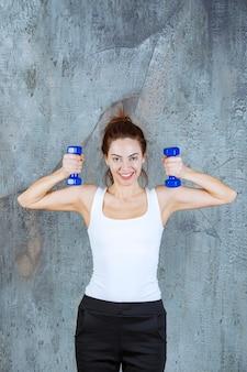 Dziewczyna za pomocą fioletowych hantli aerobowych do pilatesu na mięśnie ramion.