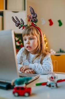 Dziewczyna Za Pomocą Laptopa Do Połączenia Wideo W Pokoju Dziecięcym W Czasie świąt Bożego Narodzenia Premium Zdjęcia