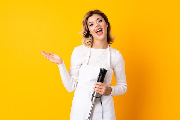 Dziewczyna za pomocą miksera ręcznego na białym tle na żółtej ścianie z zszokowanym wyrazem twarzy