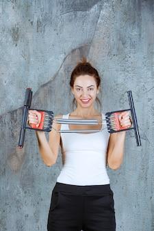 Dziewczyna za pomocą napinaczy mięśni ramion i barków w kulturystyce.