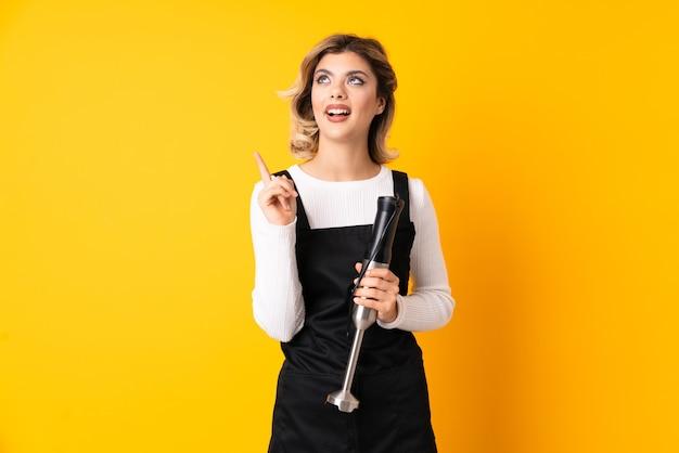 Dziewczyna za pomocą ręcznego blendera na białym tle na żółtej ścianie, która zamierza wykonać rozwiązanie, podnosząc palec