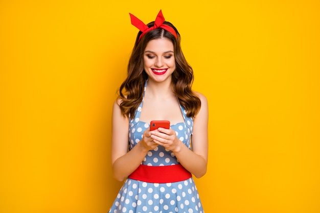 Dziewczyna za pomocą smartfona czyta wiadomości z mediów społecznościowych na żółtym tle
