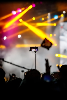 Dziewczyna za pomocą smartfona na statywie, aby nagrać film na koncercie.