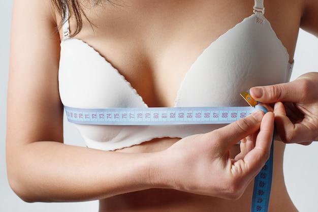 Dziewczyna za pomocą taśmy mierniczej do pomiaru obwodu klatki piersiowej