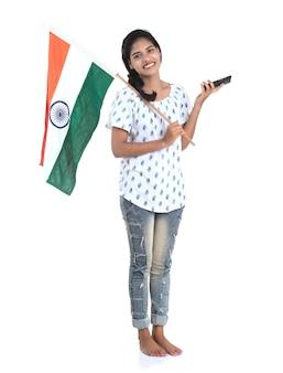 Dziewczyna za pomocą telefonu komórkowego z flagą indii lub tricolor na białej ścianie, dzień niepodległości indii, dzień republiki indii