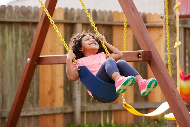 Dziewczyna za toddler dziecko kołysząc się na huśtawce plac zabaw dla dzieci