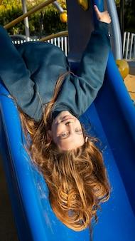 Dziewczyna, zabawy na slajdzie na świeżym powietrzu