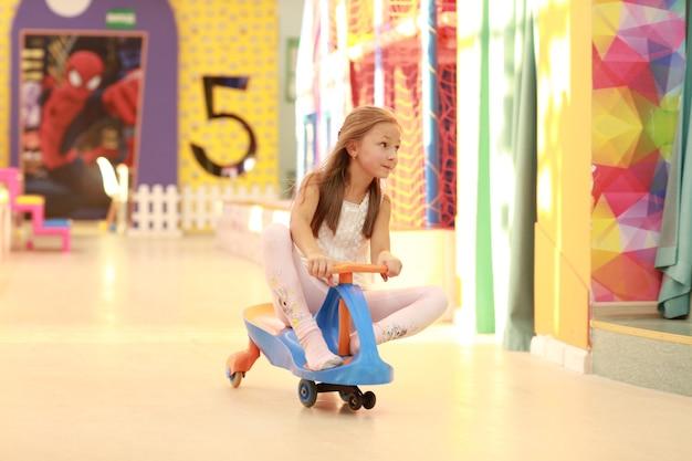 Dziewczyna, zabawy w centrum gier, jazda na rowerze.