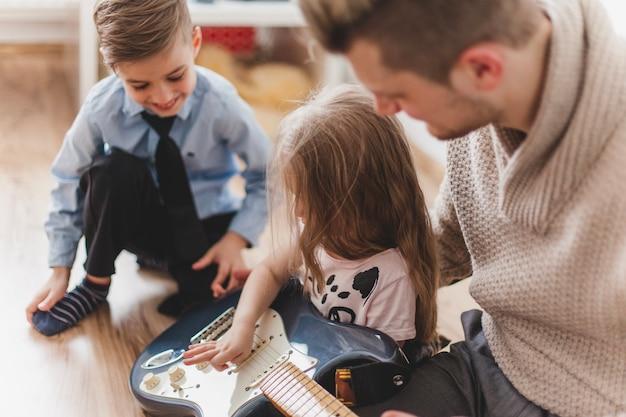 Dziewczyna zabawy z gitarą ojca